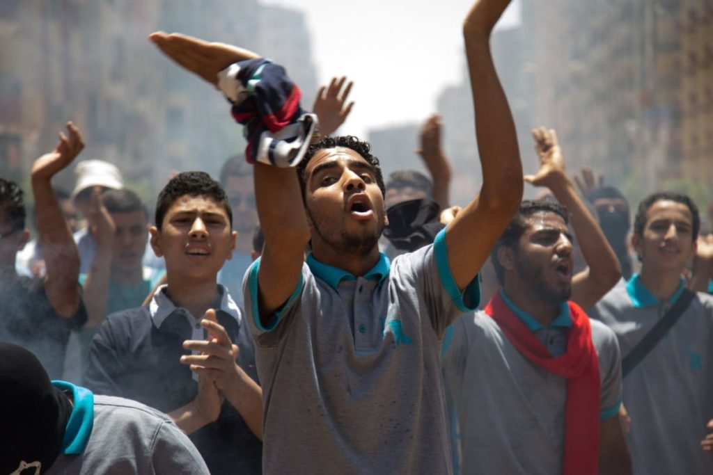 GIZA, EGYPT - JULY 3: Egyptians, who call themselves as an anti-coup group, shout slogans and light flares as they protest against the coup regime and the mass death sentence decisions including Egypt's former president Mohamed Morsi, in Giza, Egypt on July 3, 2015.