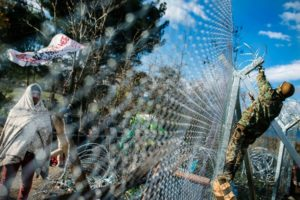 A migrant demonstrator looks on from behind a fence as he wait to cross the Greek-Macedonian border