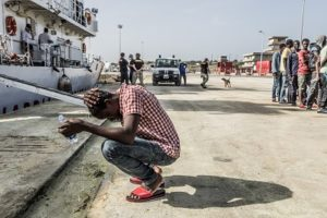 Refugee outside ship at dock in Greece