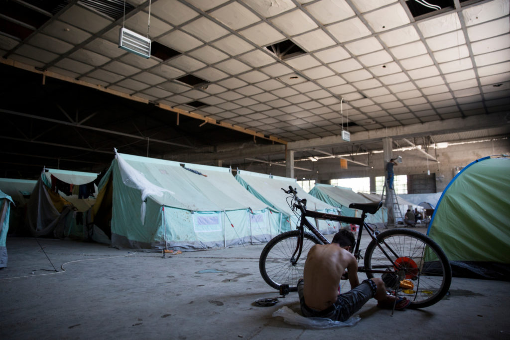 The Softex refugee camp in Sindos, near Thessaloniki, 13 July 2016. The camp houses over 1800 people from Syria, Iraq, Afghanistan and Morocco including 500 children. The camp gives the feel of a prison and barbed wire divides its different sections. Conditions are dire and refugees often find snakes around their tents. People at the camp fear for their safety as violent fights break out every day and women live in fear of being assaulted.
