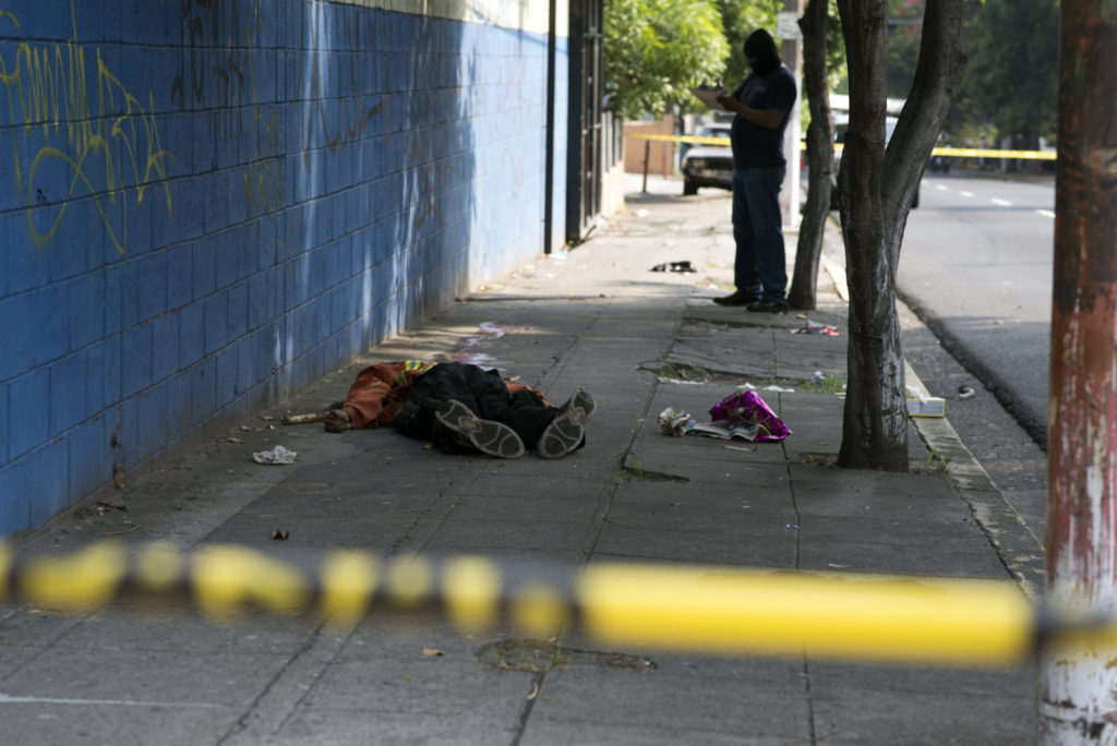 A police officer gathers information after a man was shot dead in the streets of San Salvador. El Salvador has become one of the countries in the world with a high murder rate outside a war conflict.