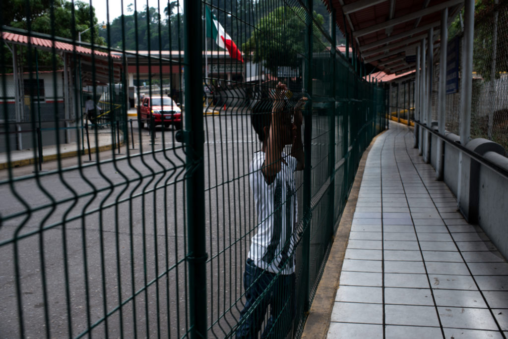 The picture at the border between Mexico and Guatemala. A boy is looking through the fence.