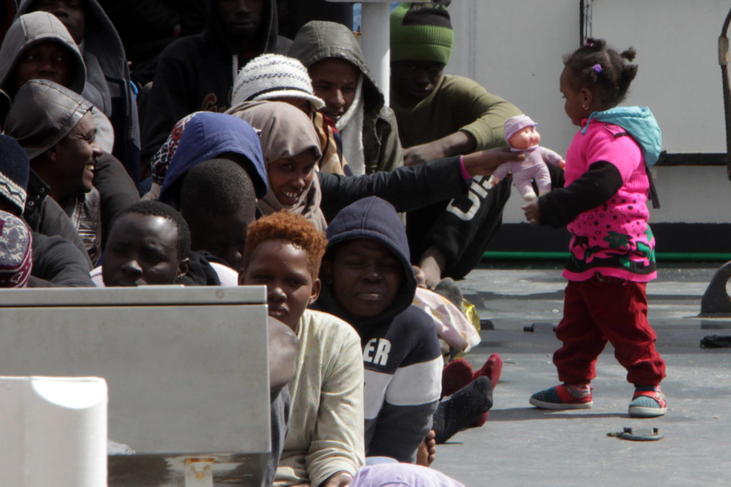 "A little girl plays with a doll as migrants and refugees wait to disembark in the port of Messina following a rescue operation at sea by the Italian Coast Guard ship ""Diciotti"" on March 17, 2016 in Sicily.  More than 2,400 migrants and three corpses have been recovered from people smugglers' boats off Libya Italy's coastguard said on March 16, 2016. After several quiet weeks, the figures represent a pick-up in the flow of migrants attempting to reach Italy via Libya, a route through which around 330,000 people have made it to Europe since the start of 2014. / AFP / GIOVANNI ISOLINO        (Photo credit should read GIOVANNI ISOLINO/AFP/Getty Images)"