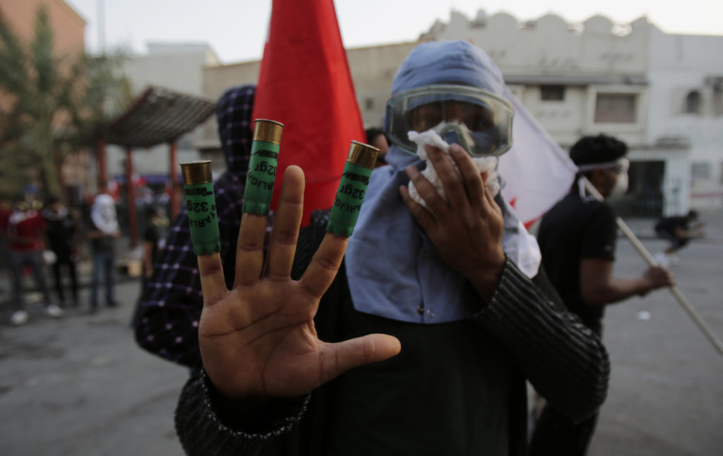 A Bahraini anti-government protester masked against tear gas show shotgun shells toward journalists during clashes between protesters throwing stones and riot police firing tear gas and shotguns in Bilad al-Qadeem, Bahrain, Friday, Jan. 16, 2015. Daily clashes have been escalating since the arrest of Shiite opposition leader Sheikh Ali Salman on Dec. 28. (AP Photo/Hasan Jamali)