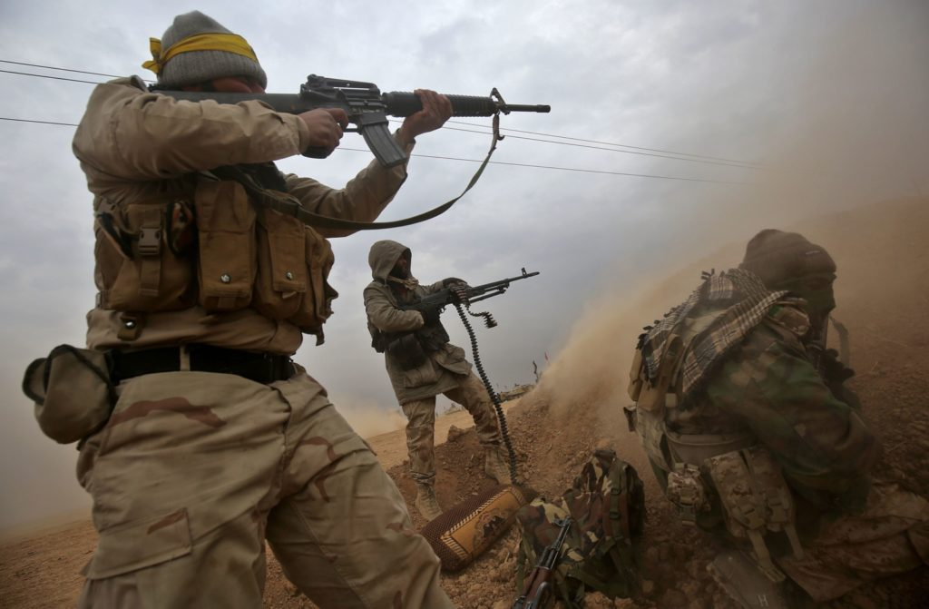 TOPSHOT - Iraqi Shiite fighters from the Hashed al-Shaabi (Popular Mobilisation) paramilitaries fire their weapons as they advance near the town of Tal Abtah, south of Tal Afar, on November 30, 2016, during a broad offencive by Iraq forces to retake the city Mosul from jihadists of the Islamic State group. / AFP / AHMAD AL-RUBAYE        (Photo credit should read AHMAD AL-RUBAYE/AFP/Getty Images)