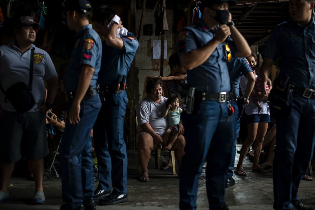"""Police officers stand as residents look at them during an """"Oplan Tokhang"""" or house-to-house campaign on illegal drugs at an informal settlers community  in Manila on October 6, 2016.  Philippine President Rodrigo Duterte told all his critics to """"go to hell"""" on October 6, as he renewed his threats to kill, after a poll showed Filipinos overwhelmingly endorsed his deadly war on crime.  / AFP / NOEL CELIS        (Photo credit should read NOEL CELIS/AFP/Getty Images)"""