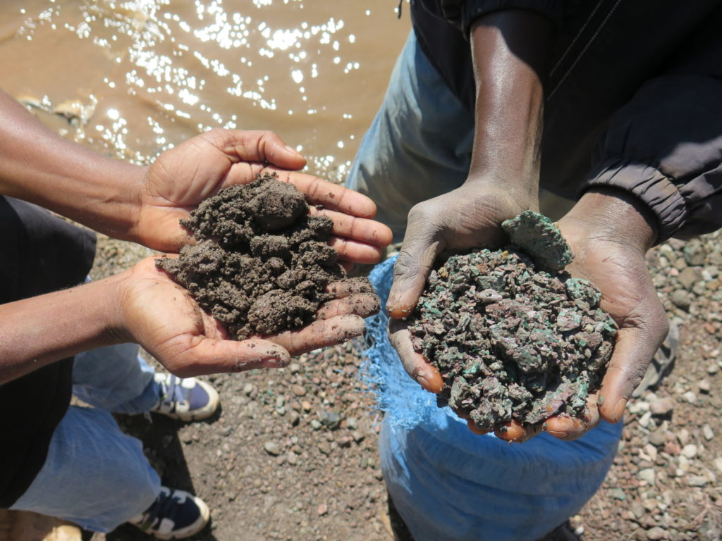 Artisanal miners hold up handfuls of cobalt ore (left) and copper ore (right) that they have scavenged from the mounds of tailings from active and inactive industrial mine sites near Lake Malo, Kapata on the outskirts of Kolwezi, in the DRC.  The miners must then sort, wash and crush the mineral ore before selling it to buying houses, May 2015.