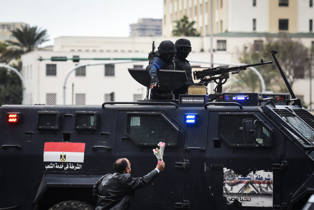 TOPSHOT - CORRECTION - A pro-government Egyptian man offers flowers to police special forces patrolling on Cairo's landmark Tahrir Square on January 25, 2016, as the country marks the fifth anniversary of the 2011 uprising. Egyptians marked the fifth anniversary of the uprising that toppled Hosni Mubarak amid tight security and a warning from the new regime that demonstrations will not be tolerated.   / AFP / MOHAMED EL-SHAHED / The erroneous mention appearing in the metadata of this photo by MOHAMED EL-SHAHED has been modified in AFP systems in the following manner: [A pro-government Egyptian man] instead of [Egyptian man]. Please immediately remove the erroneous mention[s] from all your online services and delete it (them) from your servers. If you have been authorized by AFP to distribute it (them) to third parties, please ensure that the same actions are carried out by them. Failure to promptly comply with these instructions will entail liability on your part for any continued or post notification usage. Therefore we thank you very much for all your attention and prompt action. We are sorry for the inconvenience this notification may cause and remain at your disposal for any further information you may require.        (Photo credit should read MOHAMED EL-SHAHED/AFP/Getty Images)