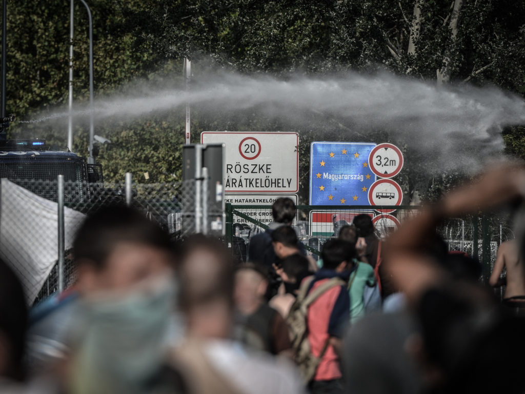 Hungarian riot police used tear gas and water cannons on migrants who tried to broke through a razor wire fence the Serbia-Hungary border in Horgos, on September 16, 2015. UN Secretary-General Ban Ki-moon on Wednesday slammed Hungary's treatment of migrants as unacceptable after police fired tear gas and water cannon at asylum-seekers at its border with Serbia. © NurPhoto/NurPhoto/Getty Images