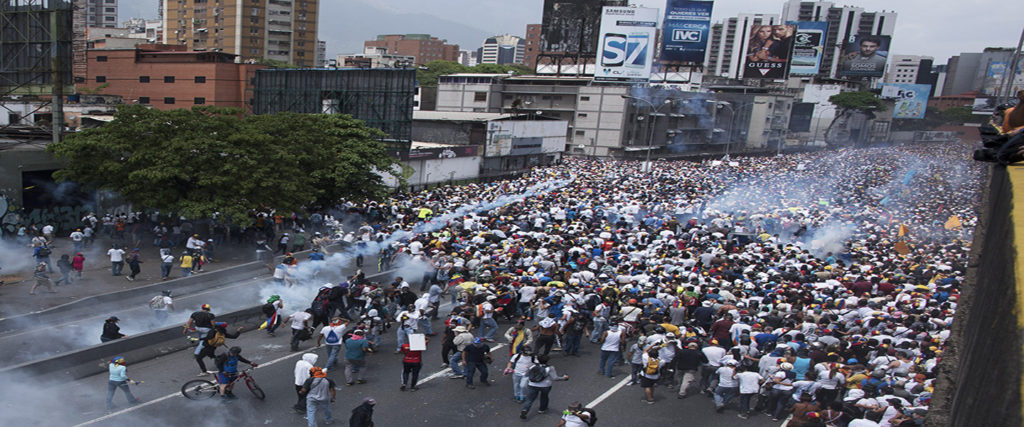 Demonstrators clash with riot police during a march against Venezuelan President Nicolas Maduro, in Caracas on April 19, 2017. Venezuelans took to the streets Wednesday for massive demonstrations for and against President Nicolas Maduro, whose push to tighten his grip on power has triggered deadly unrest that has escalated the country's political and economic crisis. / AFP PHOTO / CARLOS BECERRA        (Photo credit should read CARLOS BECERRA/AFP/Getty Images)
