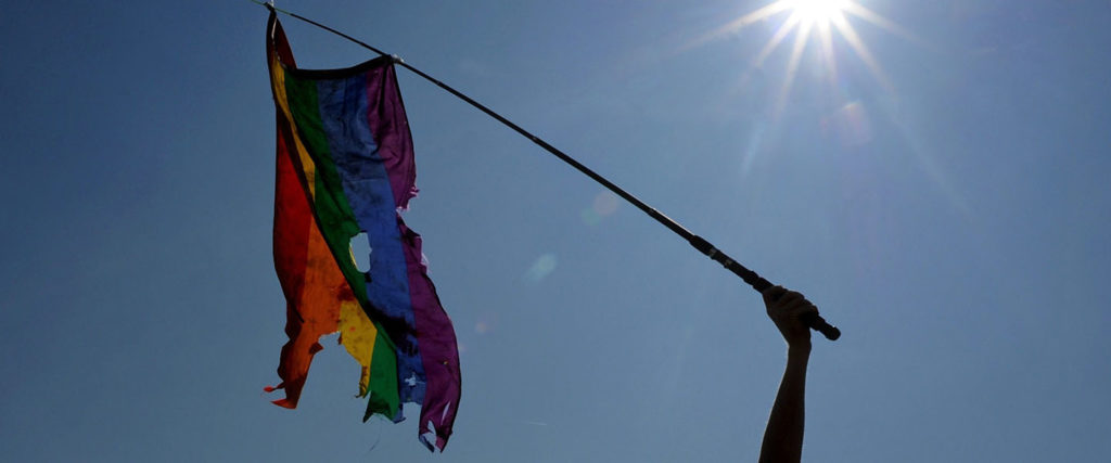 Gay rights activist waves a damaged rainbow flag during a gay pride in Russia