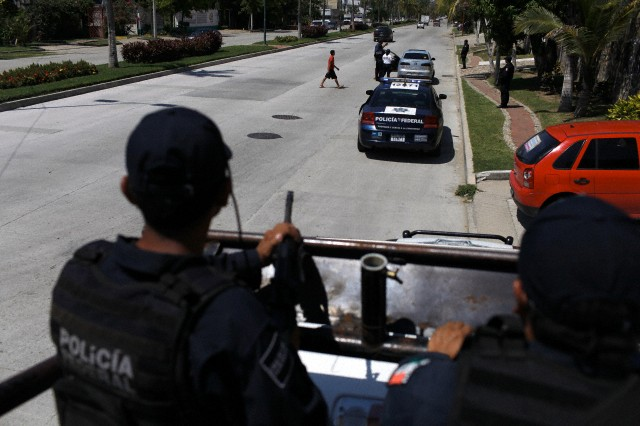 22 Oct 2011, Acapulco, Mexico --- Federal policemen stand guard atop a vehicle as his colleagues inspect a vehicle at a checkpoint in the coastal avenue in Acapulco October 22, 2011. The federal police set up a series of mobile checkpoints and aerial surveillance along the coastal avenue in this Pacific coast resort as part of the operation 'Guerrero Seguro' in order to protect tourists and general population and curb down drug related violence, local media reported. REUTERS/Tomas Bravo (MEXICO - Tags: CIVIL UNREST CRIME LAW) --- Image by © TOMAS BRAVO/Reuters/Corbis