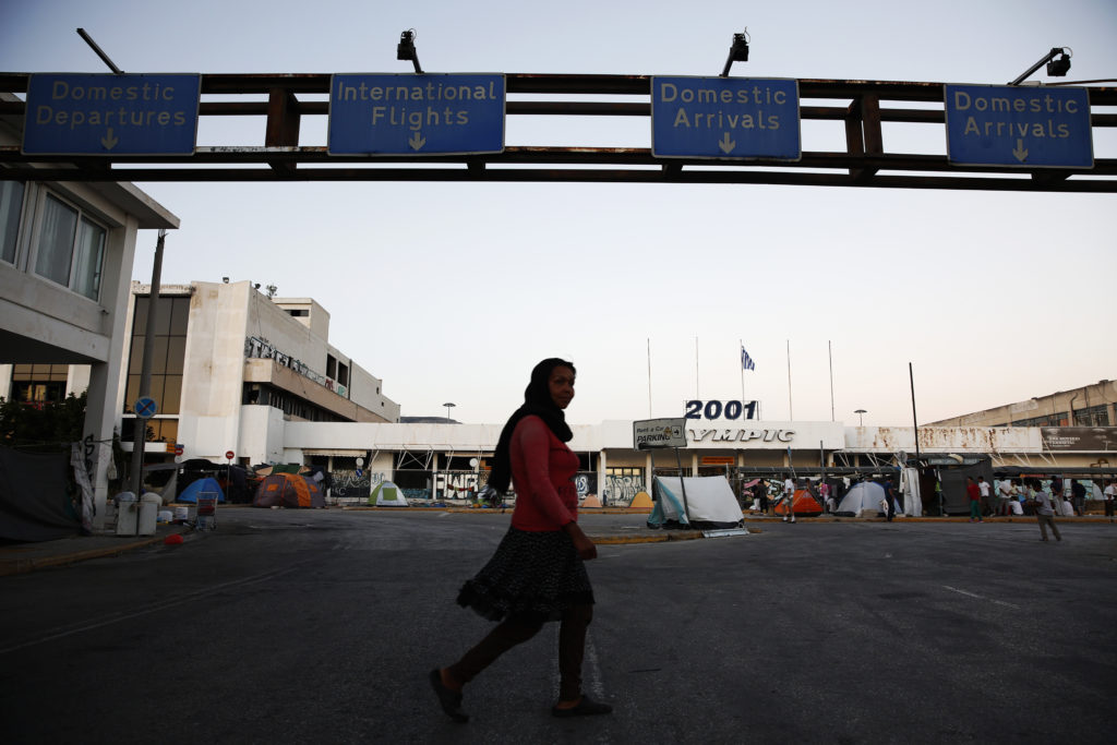 More than a thousand of refugees and migrants  have been living for over a year in three camps in Elliniko, in Athens, in substandard conditions. The majority of residents are from Afghanistan. Lack of safety and security, particularly for women and girls, is a massive concern.  The image features the outside of one of the camps: the arrivals hall of an unused airport. This image was taken in July 2016 where many of the residents were living outside the building due to overcrowding and lack of ventilation inside.