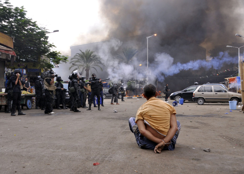A handcuffed protester sits on the ground as Egyptian security forces move in to disperse supporters of Egypt's ousted president Mohamed Morsi by force in a huge camp in Cairo's Al-Nahda square on August 14, 2013. The operation began shortly after dawn when security forces surrounded the sprawling Rabaa al-Adawiya camp in east Cairo and a similar one at Al-Nahda square, in the centre of the capital, launching a long-threatened crackdown that left dozens dead. AFP PHOTO / ENGY IMAD        (Photo credit should read Engy Imad/AFP/Getty Images)