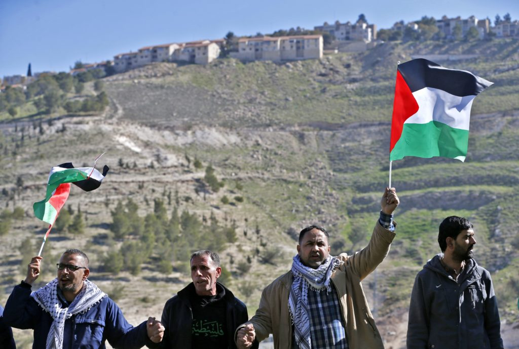 Palestinian protesters wave national flags during a demonstration against the construction of Jewish settlements in the occupied West Bank and against US President-elect Donald Trump, on January 20, 2017, near the settlement of Maale Adumim, east of Jerusalem. / AFP / ABBAS MOMANI        (Photo credit should read ABBAS MOMANI/AFP/Getty Images)