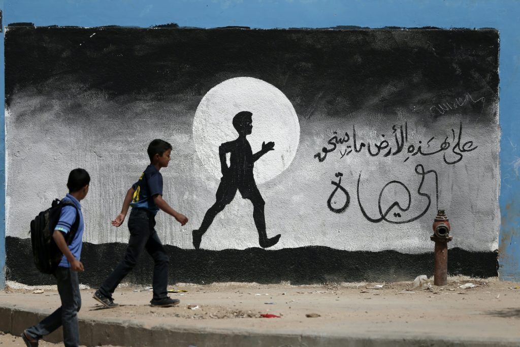 Two Palestinian schoolboys walk past a graffiti painted on a wall of the United Nations school of Beit Hanun, in the northern Gaza Strip, on May 9, 2016.  / AFP / THOMAS COEX        (Photo credit should read THOMAS COEX/AFP/Getty Images)