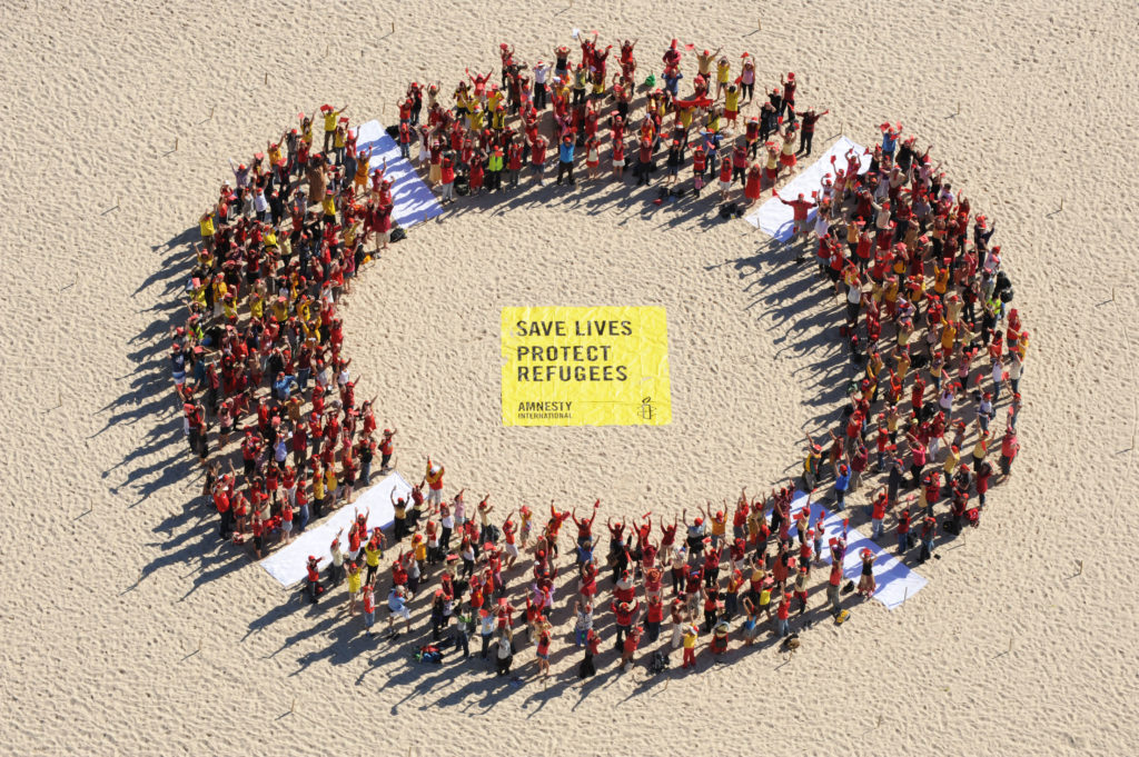 Activists gather at Bondi Beach in Sydney and other locations throughout Australia creating giant human life rings to show solidarity with refugees fleeing war and persecution, 8 May 2010. Those taking part in the events were urging the government to reverse the discriminatory freeze on processing of Sri Lankan and Afghan asylum applications, and the reopening of the remote Curtin detention centre.