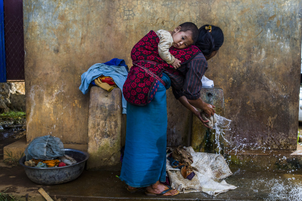 An ethnic Palaung woman carrying her child on the back, washing clothes, at Man Sar IDP camp, located on the outskirts of Kutkai, Northern Shan State, Myanmar, July 28, 2017. The camp is currently sheltering about 500 people who fled from three villages in Kutkai township. © Minzayar Oo - Panos / Amnesty International