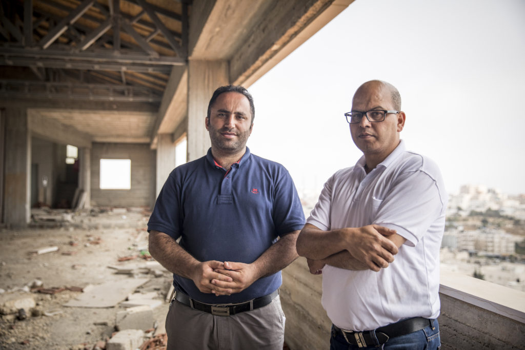"Farid al-Atrash (right) and Issa Amro (left) on a vacant floor of the building housing the Independent Commission for Human Rights, Occupied Palestinian Territories, 14 September 2017. Farid al-Atrash is the Director of the Commission's South West Bank Office.  Issa Amro and Farid al-Atrash want an end to Israeli settlements – a war crime stemming from Israel's 50-year occupation of Palestinian land. Israel has made many parts of the occupied territories no-go zones for Palestinians, making it impossible for them to move about freely. By contrast, Jewish Israeli settlers are free to go where they wish.   Dedicated to non-violence, Issa and Farid brave constant threats and attacks by Israeli soldiers and settlers. Issa encourages Palestinian youths to find non-violent ways to oppose Israel's occupation and discriminatory laws in Hebron. For this, Israeli forces have arrested him more than once. They have beaten, blindfolded, and interrogated him. ""The Israeli occupation forces target us to silence us,"" says Issa. Farid, a lawyer who exposes abuses by the Palestinian and Israeli authorities, faces similar harassment.   In February 2016, Issa and Farid joined a peaceful protest in the city of Hebron marking 22 years since Israel first closed one of its streets, al-Shuhada, to Palestinians. Hebron's 200,000 Palestinians are effectively held hostage by the 800 Israeli settlers who live in its centre. The men now face ludicrous charges clearly designed to obstruct their human rights work."