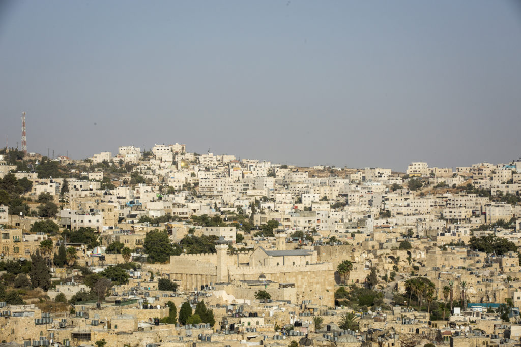"""View of Hebron from The Centre for Youth Against Settlements in Hebron, 13 September, 2017. The center is based in an old Palestinian house that used to be an Israeli military base, once the soldiers left the settlers tried to take it, occupying it several times. The YAS group decided to fight and resist the occupation, and after several direct actions and legal challenges the Israeli court finally recognised the building as a legitimate Palestinian property.  Issa Amro and Farid al-Atrash want an end to Israeli settlements – a war crime stemming from Israel's 50-year occupation of Palestinian land. Israel has made many parts of the occupied territories no-go zones for Palestinians, making it impossible for them to move about freely. By contrast, Jewish Israeli settlers are free to go where they wish.   Dedicated to non-violence, Issa and Farid brave constant threats and attacks by Israeli soldiers and settlers. Issa encourages Palestinian youths to find non-violent ways to oppose Israel's occupation and discriminatory laws in Hebron. For this, Israeli forces have arrested him more than once. They have beaten, blindfolded, and interrogated him. """"The Israeli occupation forces target us to silence us,"""" says Issa. Farid, a lawyer who exposes abuses by the Palestinian and Israeli authorities, faces similar harassment.   In February 2016, Issa and Farid joined a peaceful protest in the city of Hebron marking 22 years since Israel first closed one of its streets, al-Shuhada, to Palestinians. Hebron's 200,000 Palestinians are effectively held hostage by the 800 Israeli settlers who live in its centre. The men now face ludicrous charges clearly designed to obstruct their human rights work."""