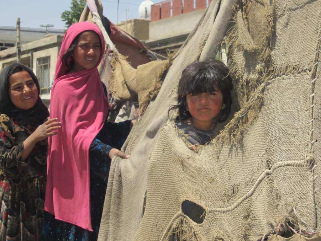 Young girls residents of a slum area of internally displaced people, in their makeshift home, located in Kart-e- Parwan area in Kabul. The photograph was taken by Amnesty International delegates during visit to the camp in June 2011.