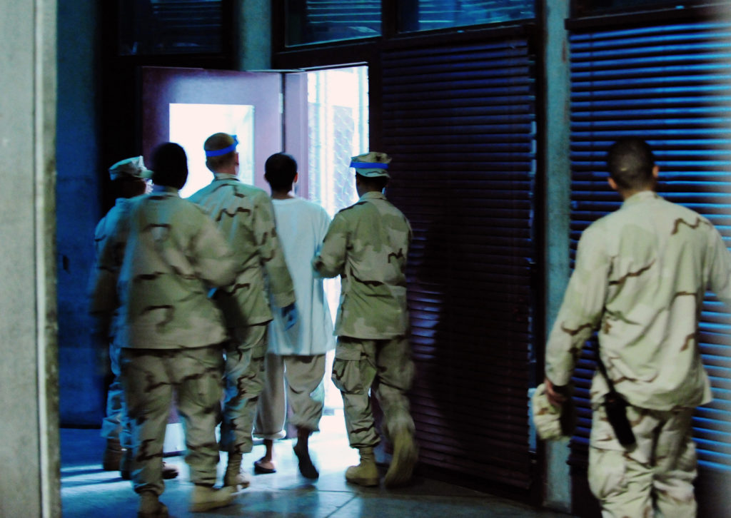 Guards at Joint Task Force Guantanamo escort a detainee inside the communal facility of Camp 6, Guantanamo Bay, Cuba, 9 October 2011.