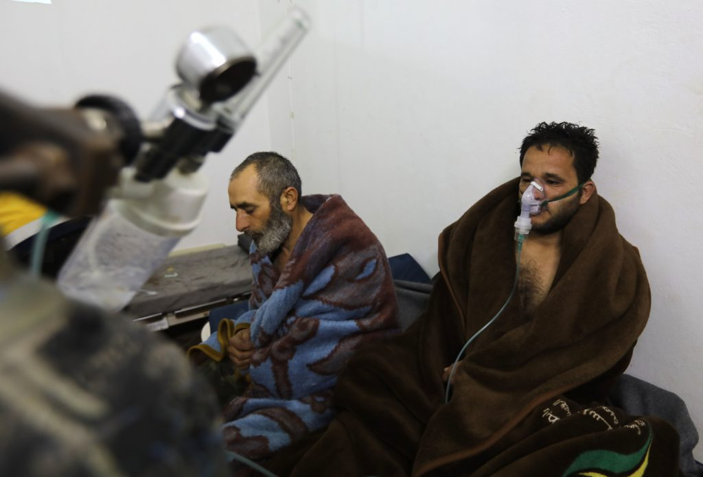 "TOPSHOT - Syrians reportedly suffering from breathing difficulties following Syrian regime air strikes on the northwestern town of Saraqeb rest around a stove at a field hospital in a village on the outskirts of Saraqeb, due to the lack of hospitals in the town, on February 4, 2018. Five people were treated for ""suffocation"" after Syrian regime air strikes on the northwestern town of Saraqeb, the Britain-based Syrian Observatory for Human Rights reported, adding that 10 civilians were killed in southern Idlib province. / AFP PHOTO / OMAR HAJ KADOUR        (Photo credit should read OMAR HAJ KADOUR/AFP/Getty Images)"