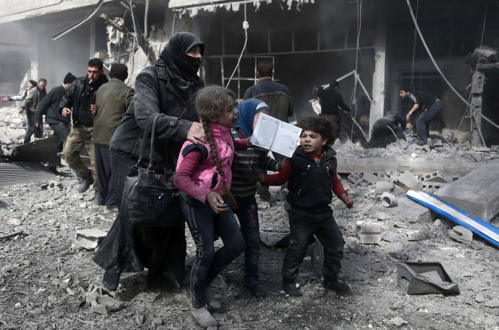 A Syrian woman and children run for cover amid the rubble of buildings following government bombing in the rebel-held town of Hamouria, in the besieged Eastern Ghouta region on the outskirts of the capital Damascus, on February 19, 2018. Heavy Syrian bombardment killed 44 civilians in rebel-held Eastern Ghouta, as regime forces appeared to prepare for an imminent ground assault. / AFP PHOTO / ABDULMONAM EASSA
